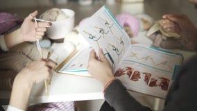 Χέρι σχεδιαστών μόδας που δείχνει στο σκίτσο ενδυμάτων στο βιβλίο φιλμ μικρού μήκους
