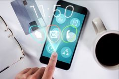 Χέρι σχετικά με το εικονίδιο στην οθόνη smartphone στην πιστωτική κάρτα, τα γυαλιά και το κλίμα φλιτζανιών του καφέ Στοκ φωτογραφίες με δικαίωμα ελεύθερης χρήσης