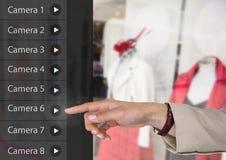Χέρι σχετικά με App κάμερων ασφαλείας το κατάστημα ενδυμάτων διεπαφών Στοκ Φωτογραφίες