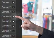 Χέρι σχετικά με App κάμερων ασφαλείας το κατάστημα ενδυμάτων διεπαφών Στοκ εικόνες με δικαίωμα ελεύθερης χρήσης