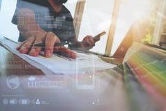 Χέρι σχεδιαστών που λειτουργεί με το φορητό προσωπικό υπολογιστή και το έξυπνο τηλέφωνο Στοκ Φωτογραφία