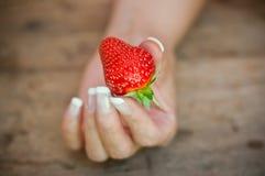 Χέρι της γυναίκας με τις φράουλες στο ξύλινο επιτραπέζιο υπόβαθρο στοκ εικόνες