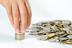 Χέρι της γυναίκας που βάζει το νόμισμα στο σωρό αύξησης των νομισμάτων, που σώζει mone Στοκ Εικόνα