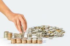 Χέρι της γυναίκας που βάζει το νόμισμα στο σωρό αύξησης των νομισμάτων, που σώζει mone Στοκ Φωτογραφία