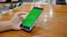 Χέρι της γυναίκας χρησιμοποιώντας το κινητό smartphone με το κενό πράσινο όργανο ελέγχου οθόνης και ακολουθώντας το σημάδι για τη φιλμ μικρού μήκους