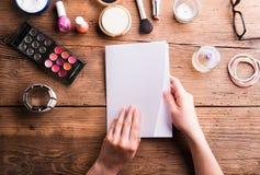 Χέρι της ευχετήριας κάρτας εκμετάλλευσης γυναικών αποτελέστε τα προϊόντα Στοκ φωτογραφία με δικαίωμα ελεύθερης χρήσης