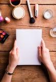 Χέρι της ευχετήριας κάρτας εκμετάλλευσης γυναικών αποτελέστε τα προϊόντα Στοκ Εικόνες