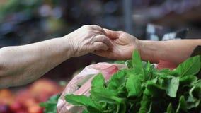 Χέρι της ηλικιωμένης πληρωμής γυναικών με ένα νόμισμα χρημάτων φιλμ μικρού μήκους