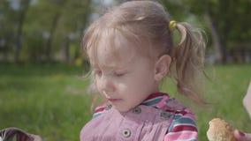 Χέρι της νέας μητέρας που ταΐζει τη χαριτωμένη ξανθή κόρη της στο πάρκο με ένα μπισκότο κοντά επάνω Ενεργός υγιής τρόπος ζωής φιλμ μικρού μήκους