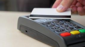 Χέρι της πληρωμής πελατών με την ανέπαφη πιστωτική κάρτα με την τεχνολογία NFC φιλμ μικρού μήκους