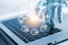 Χέρι της ρομποτικής που συνδέει με το βιομηχανικό δίκτυο στο lap-top στοκ φωτογραφίες