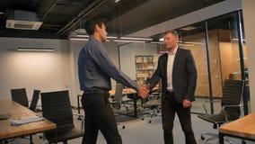 Χέρι τινάγματος δύο επιχειρηματιών ο ένας στον άλλο στην αρχή απόθεμα βίντεο