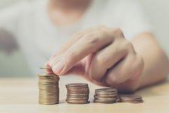 Χέρι του αρσενικού που βάζει το χρυσό σωρό νομισμάτων, τη χρηματοδότηση και το καπνιστό πικάντικο λουκάνικο επένδυσης στοκ εικόνες
