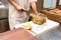 Χέρι του αρχιμάγειρα που κόβει το πράσινο ψωμί τσαγιού στο λευκό πίνακα στοκ φωτογραφία με δικαίωμα ελεύθερης χρήσης