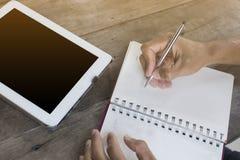 Χέρι του ασιατικού ατόμου που κρατά μια μάνδρα και που γράφει μια λέξη σε ένα σημειωματάριο Στοκ Εικόνες