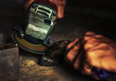 Χέρι του ατόμου με το εργαλείο κοπτών χάλυβα που θολώνεται στο μαύρο υπόβαθρο Στοκ Φωτογραφία