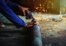 Χέρι του ατόμου με το εργαλείο κοπτών χάλυβα που θολώνεται στο μαύρο υπόβαθρο Στοκ Φωτογραφίες