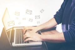 Χέρι του ατόμου που δακτυλογραφεί και που στέλνει το μήνυμα και το lap-top με το μάρκετινγκ ηλεκτρονικού ταχυδρομείου εικονιδίων  στοκ φωτογραφία
