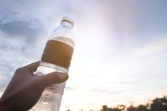 Χέρι του ατόμου που κρατά ένα μπουκάλι νερό στοκ εικόνα με δικαίωμα ελεύθερης χρήσης
