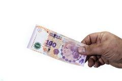 Χέρι του ατόμου που κρατά ενός εκατό τον αργεντινό λογαριασμό πέσων στον οποίο στοκ φωτογραφία