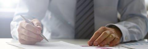 Χέρι του επιχειρηματία στο κοστούμι που γεμίζει και που υπογράφει με στοκ φωτογραφίες