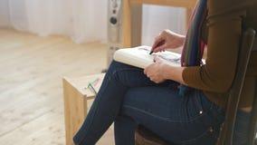 Χέρι του θηλυκού προτύπου σχεδίων καλλιτεχνών στο έγγραφο στο ελαφρύ στούντιο απόθεμα βίντεο