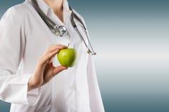 Χέρι του θηλυκού γιατρού που κρατά το πράσινο μήλο Κλείστε αυξημένος στο γκρι στοκ εικόνες