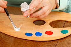 Χέρι του καλλιτέχνη που βάζει το χρώμα πέρα από την παλέτα Στοκ εικόνα με δικαίωμα ελεύθερης χρήσης