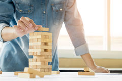 Χέρι του μηχανικού που παίζει ένα ξύλινα παιχνίδι & x28 πύργων φραγμών jenga& x29  στο blu Στοκ φωτογραφίες με δικαίωμα ελεύθερης χρήσης