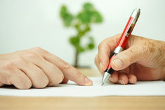 Χέρι του νέου ενηλίκου που δείχνει το ηλικιωμένο πρόσωπο πού να υπογράψει Στοκ Εικόνα