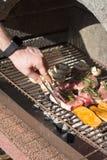 Χέρι του νεαρού άνδρα που ψήνει κάποια κρέας και λαχανικό στη σχάρα στοκ φωτογραφία με δικαίωμα ελεύθερης χρήσης