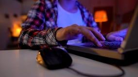 Χέρι του νευρικού αγοριού που πιέζει τα βασικά, παίζοντας τηλεοπτικά παιχνίδια στο lap-top, εθισμός στοκ εικόνα