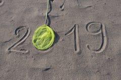 χέρι του 2019 που επισύρεται την προσοχή στην άμμο με την πεταλούδα καθαρή Το νέο έτος έρχεται ή οι διακοπές καταχωρούν το αφηρημ στοκ εικόνες