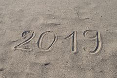 χέρι του 2019 που επισύρεται την προσοχή στην άμμο Το νέο έτος έρχεται ή οι διακοπές καταχωρούν το αφηρημένο σχέδιο υποβάθρου στοκ εικόνα