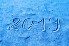 χέρι του 2019 που επισύρεται την προσοχή στην άμμο που χρωματίζεται στο μπλε Το νέο έτος έρχεται ή οι διακοπές καταχωρούν το αφηρ στοκ εικόνα