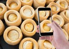 Χέρι του προσώπου που παίρνει μια εικόνα των κέικ με το smartphone της Στοκ φωτογραφία με δικαίωμα ελεύθερης χρήσης