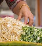 Χέρι του πωλητή οδών που προετοιμάζει τους νεαρούς βλαστούς και το scallion φασολιών για το PA Στοκ Φωτογραφίες