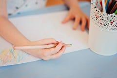 Χέρι του σχεδίου κοριτσιών παιδιών με τα μολύβια στο σπίτι Στοκ εικόνα με δικαίωμα ελεύθερης χρήσης