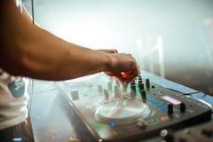 Χέρι του DJ στον αναμίκτη στη λέσχη νύχτας αναμμένη με το φωτεινό φως Στοκ Φωτογραφίες