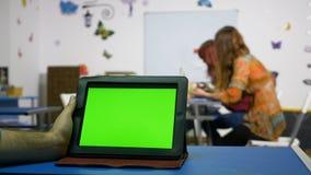 Χέρι του PC ταμπλετών εκμετάλλευσης ατόμων με την πράσινη οθόνη σε ένα δωμάτιο σειράς μαθημάτων απόθεμα βίντεο