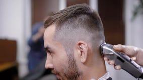 Χέρι του unrecognizable κουρέα που χρησιμοποιεί trimmer στο κεφάλι του μοντέρνου πελάτη στο σαλόνι απόθεμα βίντεο