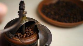 Χέρι των αλέθοντας φασολιών καφέ Barista στον εκλεκτής ποιότητας μύλο καφέ φιλμ μικρού μήκους
