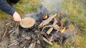 Χέρι των δημητριακών ενός γυναικών ανακατώματος που μαγειρεύουν στη φωτιά απόθεμα βίντεο