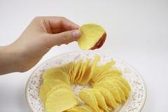 Χέρι των τσιπ πατατών με τη σάλτσα ντοματών, τσιπ πατατών στο πιάτο Διατροφή, πάχυνση στοκ φωτογραφία