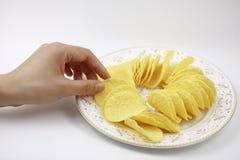 Χέρι των τσιπ πατατών, τσιπ πατατών στο πιάτο Διατροφή, πάχυνση στοκ φωτογραφία με δικαίωμα ελεύθερης χρήσης