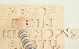 Χέρι χαριτωμένο λίγου παιδιού που παίζει με τις επιστολές στοκ εικόνες
