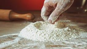 Χέρι Baker που προετοιμάζει το αλεύρι στον πίνακα για να κάνει τη ζύμη, σε αργή κίνηση, 240 fps Μαγειρεύοντας και υποστηρίζοντας  φιλμ μικρού μήκους