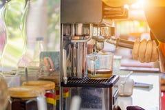 Χέρι barista γυναικών που χρησιμοποιεί να προετοιμαστεί μηχανών καφέ τον αυτόματο φρέσκο καφέ και έκχυση στο φλυτζάνι γυαλιού στοκ φωτογραφία