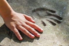 Χέρι Childs και αξιοσημείωτο handprint στο σκυρόδεμα Στοκ φωτογραφία με δικαίωμα ελεύθερης χρήσης
