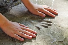 Χέρι Childs και αξιοσημείωτο handprint στο σκυρόδεμα Στοκ Φωτογραφίες